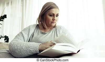 An attractive overweight woman at home, reading a book. - An...