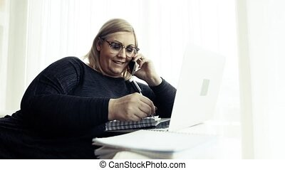 An attractive overweight woman at home, using laptop and...