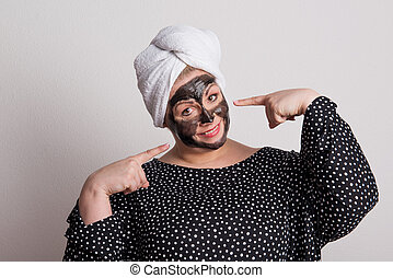 An attractive overweight woman with black facial mask on her face in a studio.