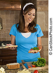 An attractive smiling woman, a typical American Mom, preparing fresh healthy sandwiches in her kitchen with ham, cheese, salad lettuce and tomatoes