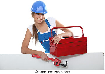 An attractive tradeswoman holding a pipe wrench and toolbox