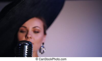 An attractive woman in big black elegant hat grabs the mic and starts singing. Bright lighting