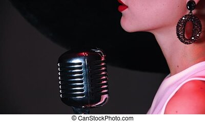An attractive woman standing by the retro mic. Red lips. Side angle. Close up