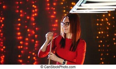 An attractive woman standing in billiard club rubbing chalk on a cue. Portrait