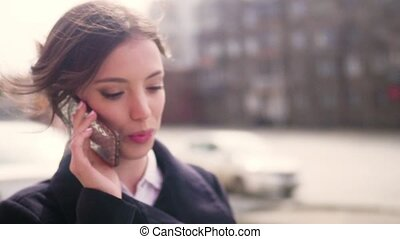 An attractive woman walks down the sidewalk while talking on her phone. close up