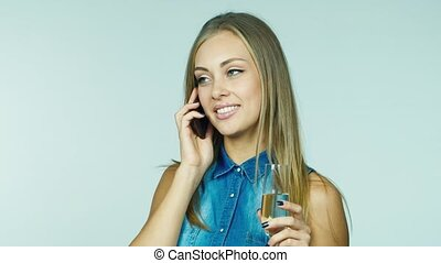 An attractive woman with a glass of champagne receiving congratulations by phone