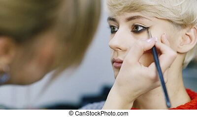An attractive woman with a short haircut applied makeup