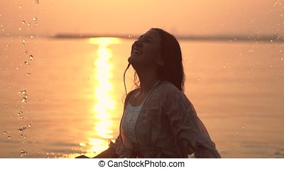 An attractive young girl makes a spray of hands standing in the water against the background of the sun having a good mood. slow motion.