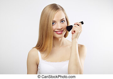 An attractive young lady applying blusher on a gray background