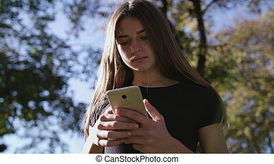 An attractive young lady using a phone in town. Medium shot