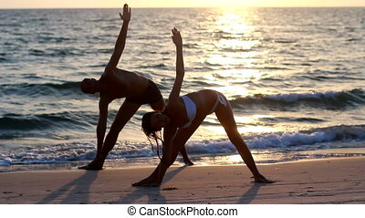 An attractive young woman and man doing yoga on a jetty with the  ocean