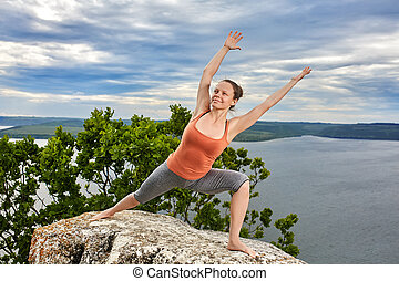 An attractive young woman doing a yoga pose for balance on the rock.