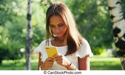An attractive young woman reads and writes messages while walking in a summer park on a sunny day