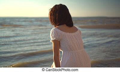 An attractive young woman sits on the beach and looks at the sea. The girl in a white dress sits with her back.