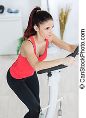 an attractive young woman using a step machine