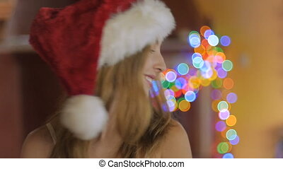 An attractive young woman wearing a santa hat twirls her hair in slow motion