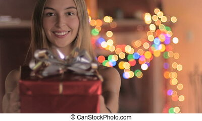 An attractive young woman wearing a Santa hat gives a wrapped gift at night