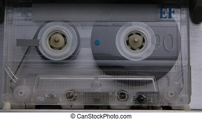 An audio cassette spools tape in extreme macro. Vintage music cassette playing back in the player. Close up. Slow motion