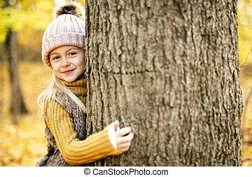 An Autumn portrait of cute blond child girl