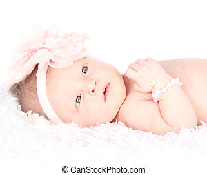 an awake newborn girl with blue eyes laying on a blanket