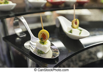 canapes cheese olives on a white plate