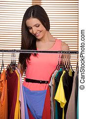 an, der, einzelhandel, store., heiter, junge frau, wählen, kleiden, in, einzelhandelsgeschäft