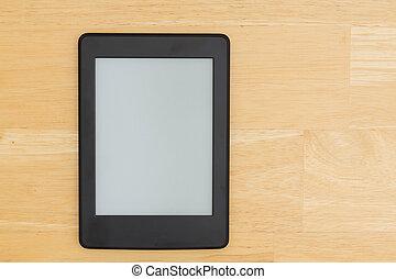 An e-reader on a wood desk