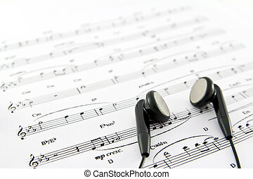 An ear phone on the top of a music sheet