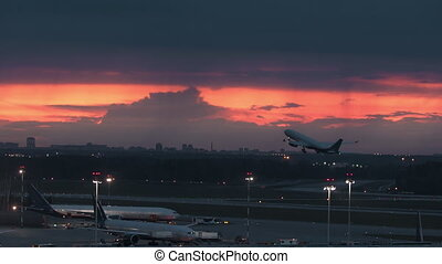 An early takeoff at an airport - a plane rises in the reddening sky, leaving two other planes below