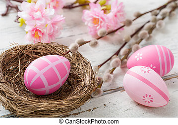 An easter nest with pink easter eggs on a wooden background