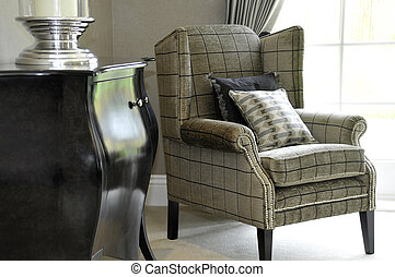 chair - An easy chair and two cushions neara window in a...