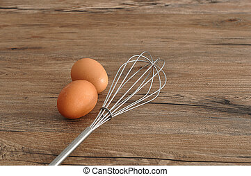 An egg beater, whisk, with two eggs isolated on a wooden background