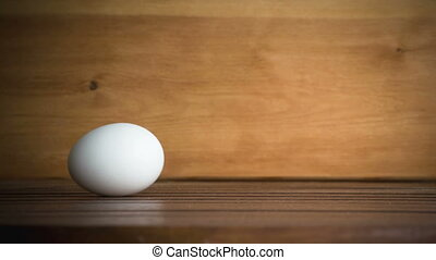 An egg is rolling across the table. Slow motion. Filmed at...