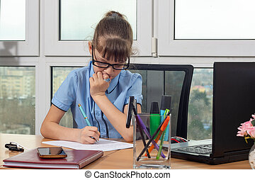 An eight-year-old girl at the table in the office thoughtfully writes a pen on a sheet of paper