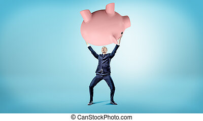 An elated businessman holds up a giant overturned piggy bank over his head.
