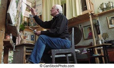 An elderly artist writes a picture in his studio 4k - An...