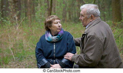 An elderly, beautiful couple talking and walking in the park. They gently smile, hug, like to look at each other.