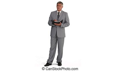 An elderly businessman jotting down notes