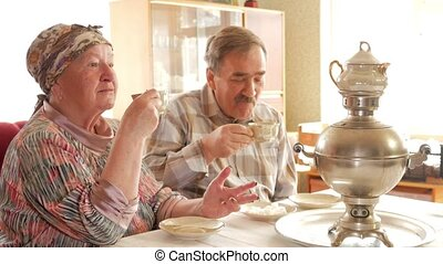 An elderly couple is drinking tea from a vintage Russian kettle samovar. A man with a mustache talking with his wife in a kerchief