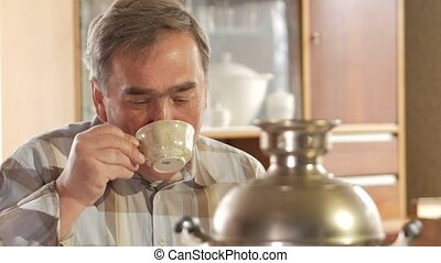 An elderly couple is drinking tea from a vintage Russian kettle samovar. A man with a mustache talking with his wife.