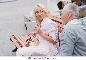 An elderly couple is resting sitting on a bench in the square. A woman holds a tablet in her hands and smiles