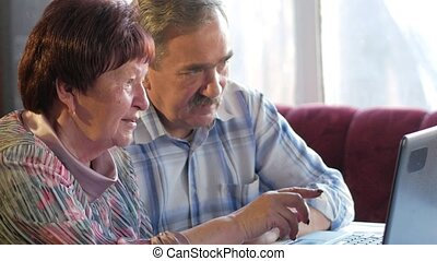 An elderly couple is sitting at home at the laptop. A woman reads news, a man with a mustache sits next to him and talks