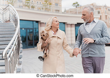 An elderly couple is walking. A woman has a dog in her arms. The man is near