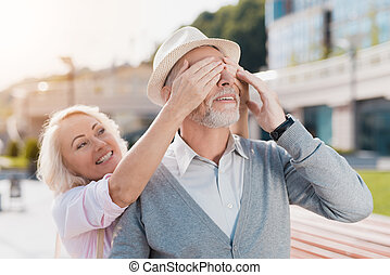 An elderly couple is walking in the square. The woman approached the man from behind and covered his eyes