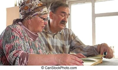 An elderly couple man and woman are looking at their old photos at home and talking. A man with a mustache, a wife with glasses