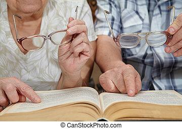 An elderly couple reading a book