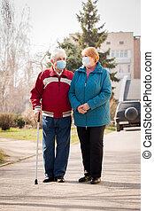 An elderly couple walk along the street during quarantine