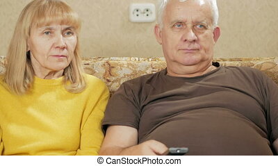 An elderly couple watching television at home on the couch. Woman laughing picks TV remote control itself and choose interesting programs. holiday home concept