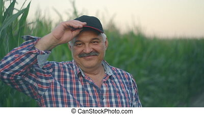 An elderly farmer films a baseball cap staring at the camera and smiling while standing in a field with corn