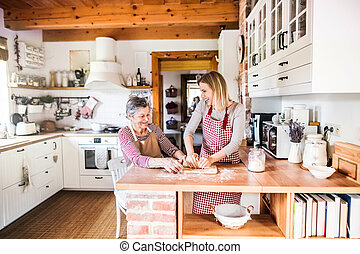 A happy elderly grandmother with an adult granddaughter at home, baking.